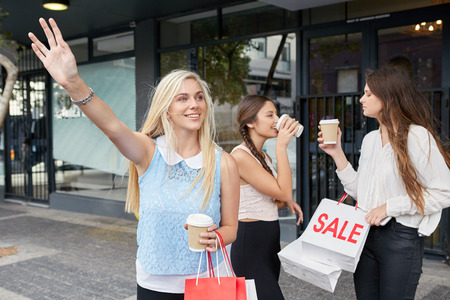 sidewalk sale: young happy girl calling for taxi cab along city sidewalk with coffee cup sale shopping bag friends