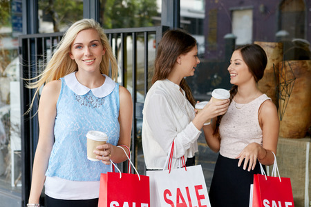 blonde teenage girl: portrait of beautiful teen girl shopping in city with friends standing outdoors