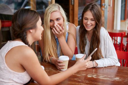 femmes souriantes: belles jeunes filles ayant caf� au caf� en plein air avec un t�l�phone mobile cellulaire Banque d'images