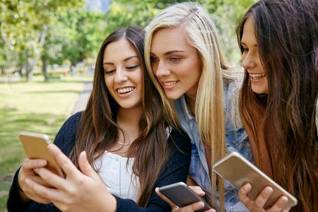야외의 모바일 휴대 전화에 바이러스 성 소셜 미디어 동영상을보고 젊은 친구 스톡 콘텐츠
