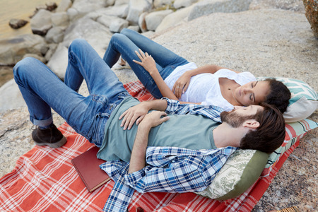couple outdoor: couple having a snooze at a picnic on the rocks, near the ocean