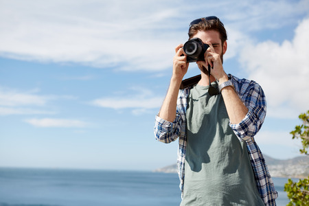 caucasion: young, attractive man standing and taking pics of the ocean using a digital camera Stock Photo