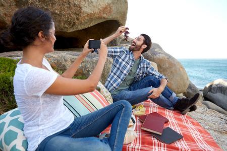 relajado: Feliz pareja tomando fotos durante un picnic relajante en las rocas, cerca del océano