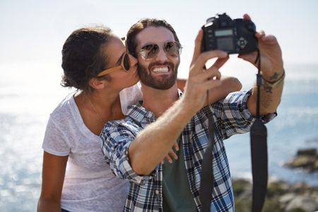 jovial: happy couple take a selfie with a kiss, with a beautiful ocean background using a digital camera Stock Photo