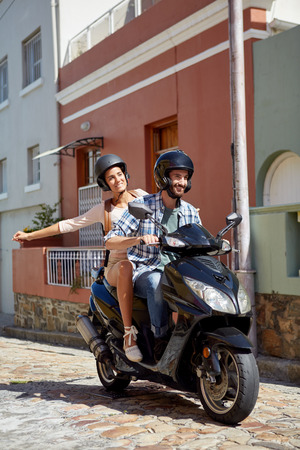 happy couple enjoying themselves on a scooter journey on holiday 스톡 콘텐츠