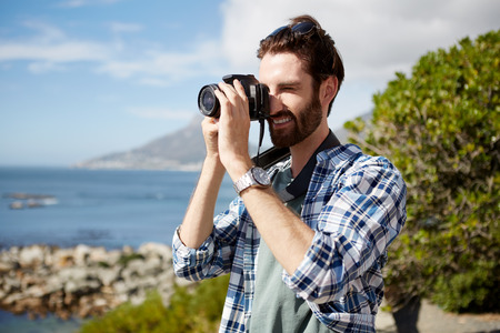 pics: young, attractive caucasian man standing and taking pics of the ocean using a digital camera