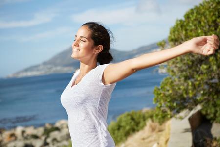 美しい幸せな女性を伸ばし、日光を採用