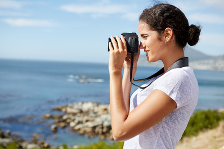 pics: young, attractive woman standing and taking pics of the ocean using a digital camera Stock Photo
