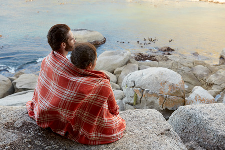 comfort: Happy, all cuddled multiracial couple, sitting on the rocks, overlooking the ocean and enjoying the view