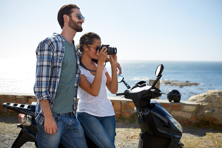 pictures: happy couple standing against a scooter, enjoying the beautiful ocean view and taking pictures
