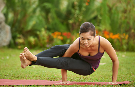 confident: strong yoga woman practise routine in park doing Astavakrasana pose