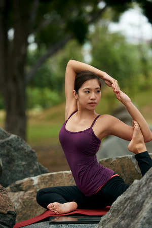 yoga rocks: young beautiful woman practicing traditional yoga poses on rocks Stock Photo