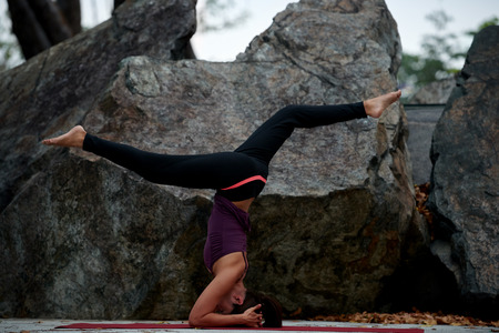yoga rocks: young fitness woman practicing yoga poses near rocks head stand Stock Photo