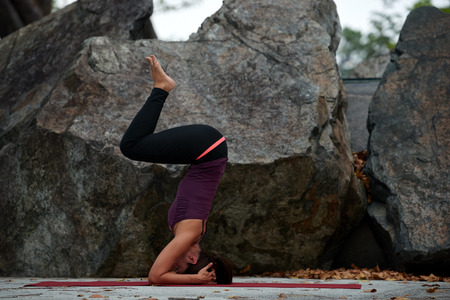 body posture: young fitness woman practicing yoga poses near rocks head stand Stock Photo