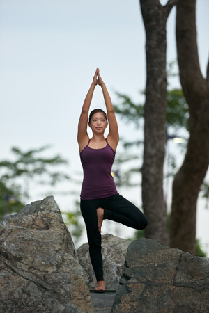 yoga rocks: young fitness woman practicing yoga balance poses on rocks