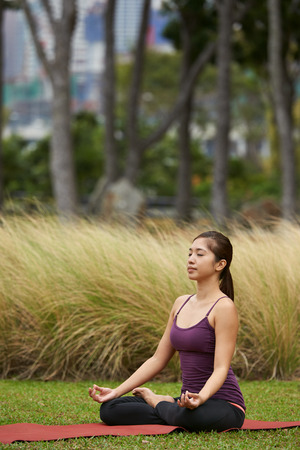 position: young fitness woman in the park doing yoga pose  meditating in lotus pose Stock Photo