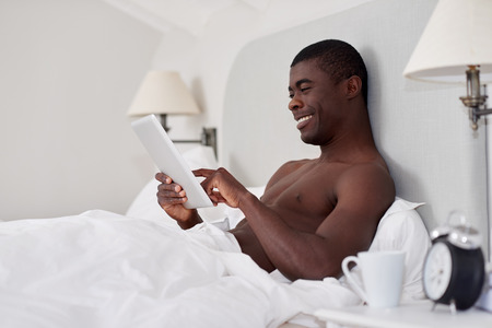 black man: handsome african black man with tablet computer sitting comfortably in bed at home