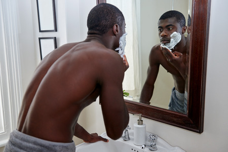 mirror: shirtless african black man applying shaving cream to face in mirror reflection for morning clean shaven look in home bathroom