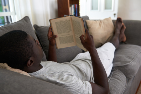 people relaxing: intellegent african black man relaxing on sofa couch reading literature novel story book at home living room lounge