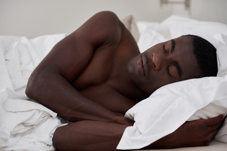 black guy: peaceful african black man sleeping comfortably in bed at home Stock Photo