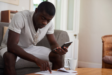 black men: african black man sitting on sofa couch calculating home bill finances in living room Stock Photo