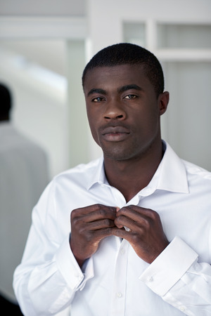 morning routine: handsome professional african black man getting ready morning routine shirt at home for work