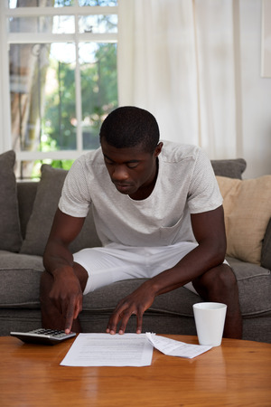 African Black Man Sitting On Sofa Couch Calculating Home Bill Finances In Living  Room Photo