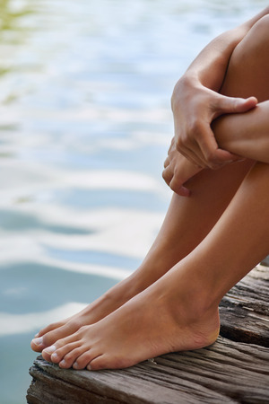 docks: Close up of female feet as she relaxes by the lake sitting on the edge of a wooden jetty, hands over her knees