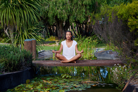 long shot: Long shot of a focussed young female sitting by a pond, lake, practising yoga Stock Photo