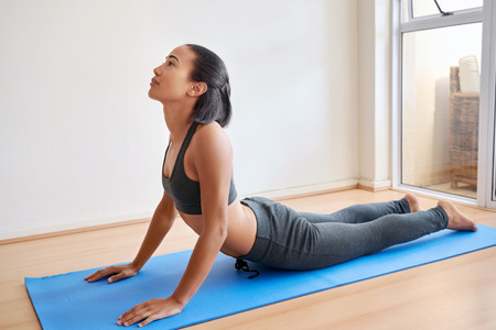 indoors: young fitness female practicing a yoga pose, position indoors