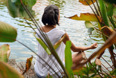 pond: Rear view of young woman in a yoga position near a lake, pond, sitting amongst the trees