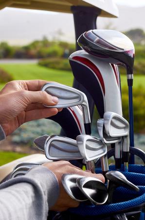 choosing: golfer choosing best club in bag