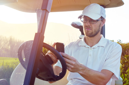 golfer: golf man relaxing on buggy cart with mobile cellphone summer vacation