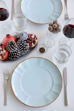 pine  fruit: Party place table setting for christmas holidays, festive with pine cones and pomegranate fruit as centrepiece