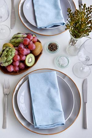Centrepiece: Simple elegant dinner place setting, using fresh fruit and vegetable kiwi grapes artichoke as centrepiece decoration