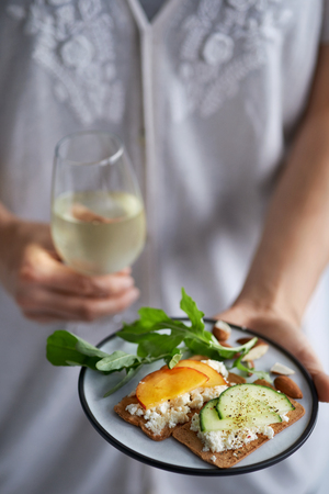 glass topped: Hands holding a glass of wine and a plate of fresh cheese canapes topped with nectarine and cucumber at a party