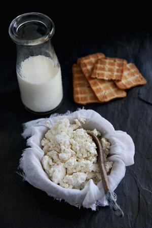 melba: Homemade drenaje requesón en tela de queso con leche de muselina principal ingrediente en el fondo oscuro Foto de archivo