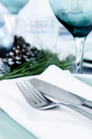 christmas table: Holiday function event table setting with blue silver white christmas theme, cutlery wine glass and napkin Stock Photo