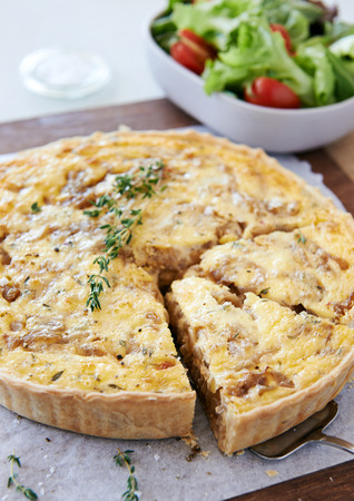 side salad: Serving slice of baked quiche tart with caramelised onions and cheese served with side salad Stock Photo
