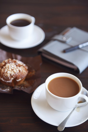daily planner: Cups of coffee with a muffin and a daily planner in the background