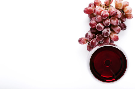 glass of red wine: Glass of red wine with bunch of grapes, overhead on white background, minimalist arrangement