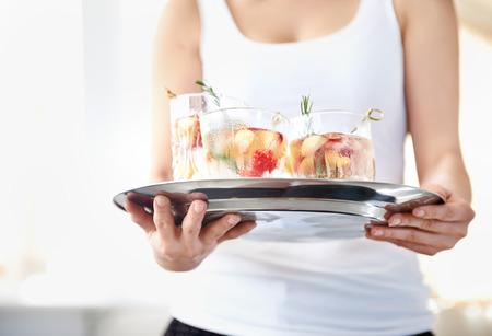bebidas frias: Recorta la imagen de una mujer que sostiene una bandeja de bebidas fr�as refrescantes con los aderezos de fruta fresca en ellos