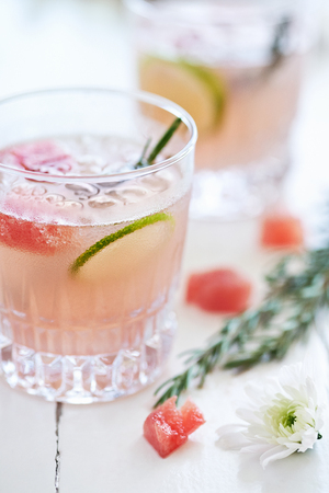 arrangment: Refreshing cool cocktail mocktail drink decorated with lime slices,watermelon and rosemary