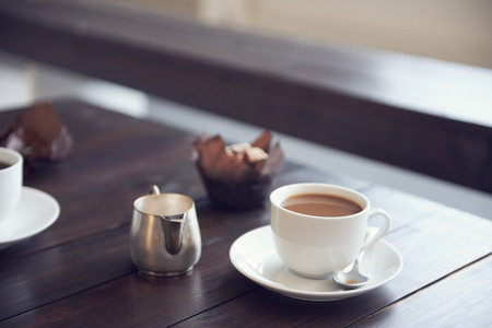 A table in a cafe with a cup and saucer with coffee in it with a muffin next to it Stok Fotoğraf