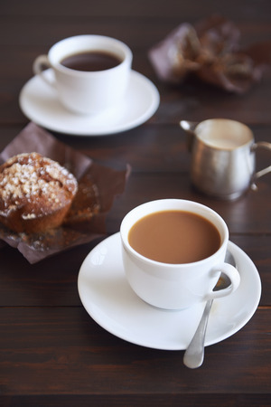 cups of coffee: Two cups of plain coffee with muffins beside them on a dark wood table