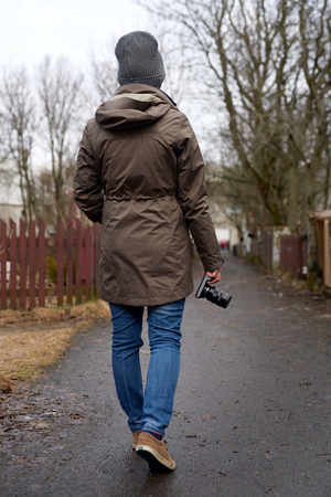 warmly: rear view of warmly dressed woman walking, holding digital camera in hand
