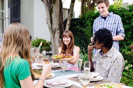 get together: Friends enjoying themselves and having fun at a party with food and alcohol, a casual lunch get together in a garden Stock Photo