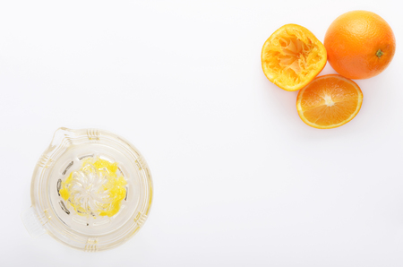 oj: Glass Juicer with cut oranges on white background, overhead perspective
