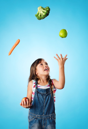 juggling: Young cute girl juggling vegetables and fruit over her head, healthy lifestyle, eating and diet concept Stock Photo