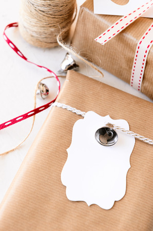 crafting: Gifts wrapped in plain paper tied with twine, silver ornaments and a blank gift tag, crafting at home for christmas valentines day